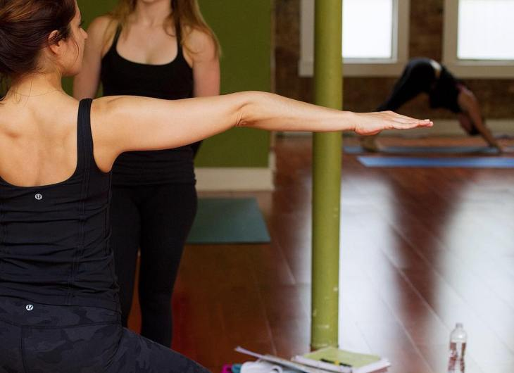 Yogi posing in front of instructor, inside the studio of Uptown Yoga