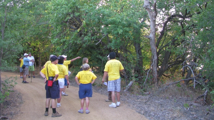 Tour group hiking shoreline trail with host pointing to trees
