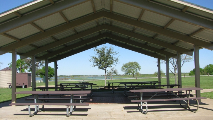 covered picnic pavillion with tables, Lewisville Lake in background
